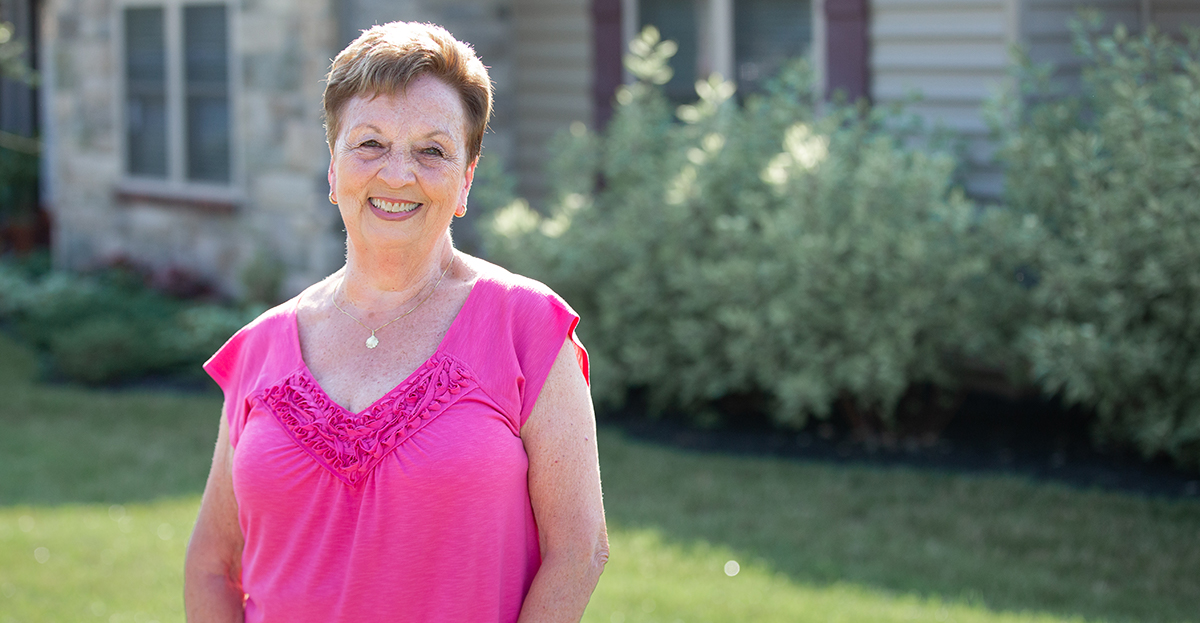 Smiling resident in front of her cottage